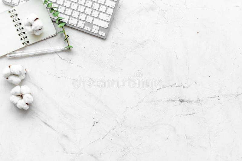 Laptop, cotton branch, notebook on white background flat lay copy space. Minimal freelancer, blogger desk workspace. stock image