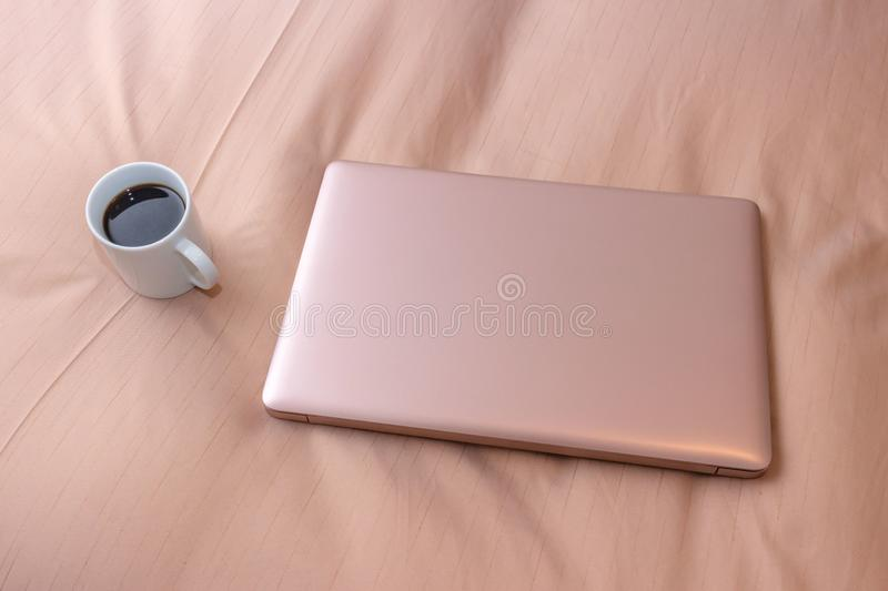 Laptop and a cup of coffee on the bed, business trip royalty free stock photography