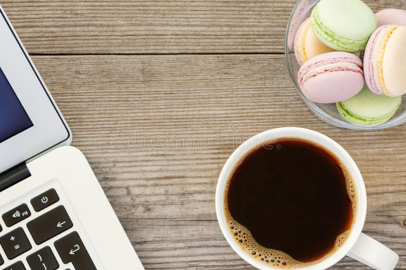 Laptop, cup of coffee and french macarons. On old wooden background royalty free stock image