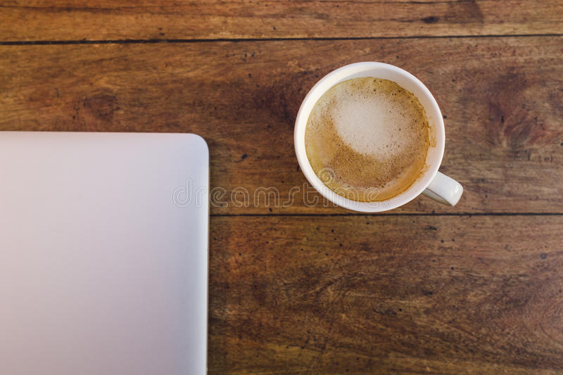 A laptop and a cup of coffee over a wood table royalty free stock photo