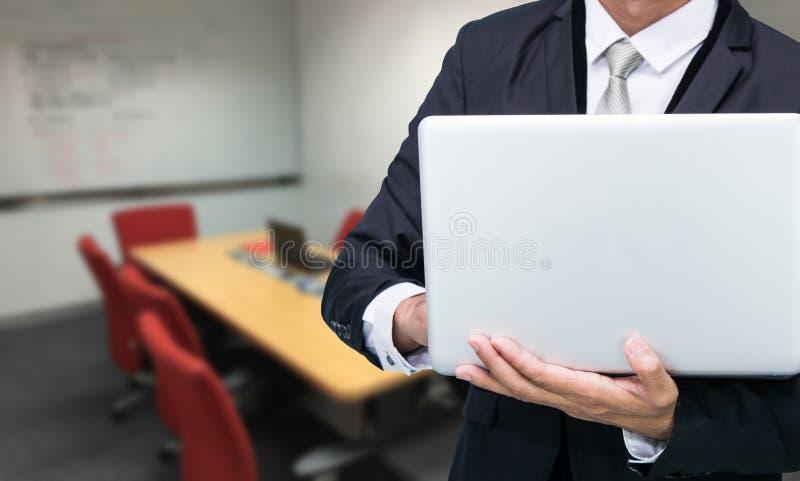 Laptop da posse do homem de negócios foto de stock