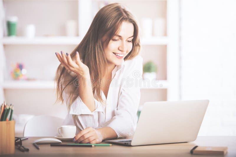 Laptop de utilização fêmea de sorriso fotografia de stock royalty free