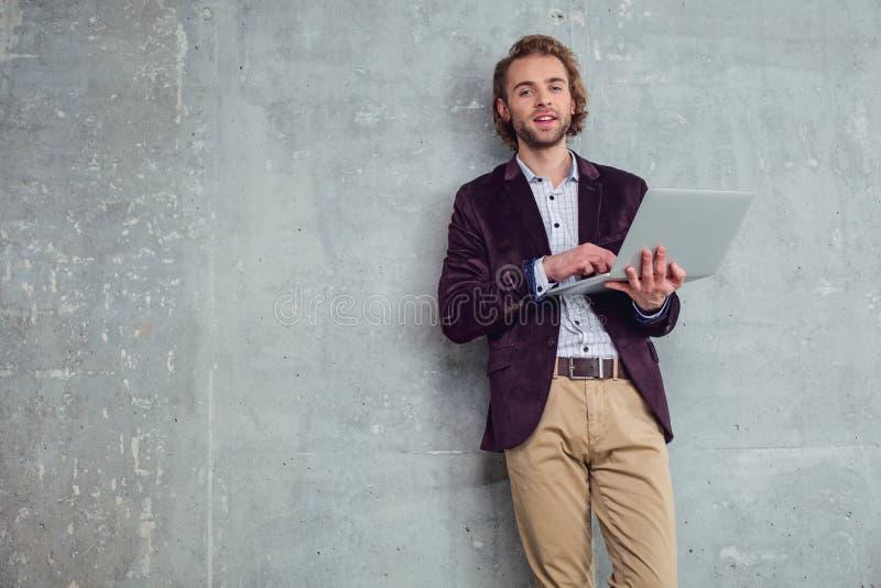 Laptop de utilização masculino alegre fotografia de stock royalty free