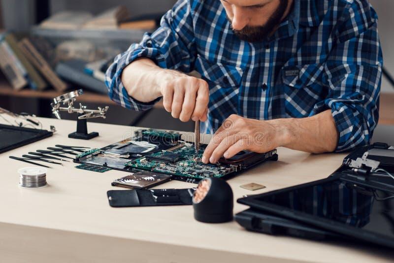 Laptop, der mit Schraubenzieher an der Reparatur auseinanderbaut lizenzfreie stockbilder