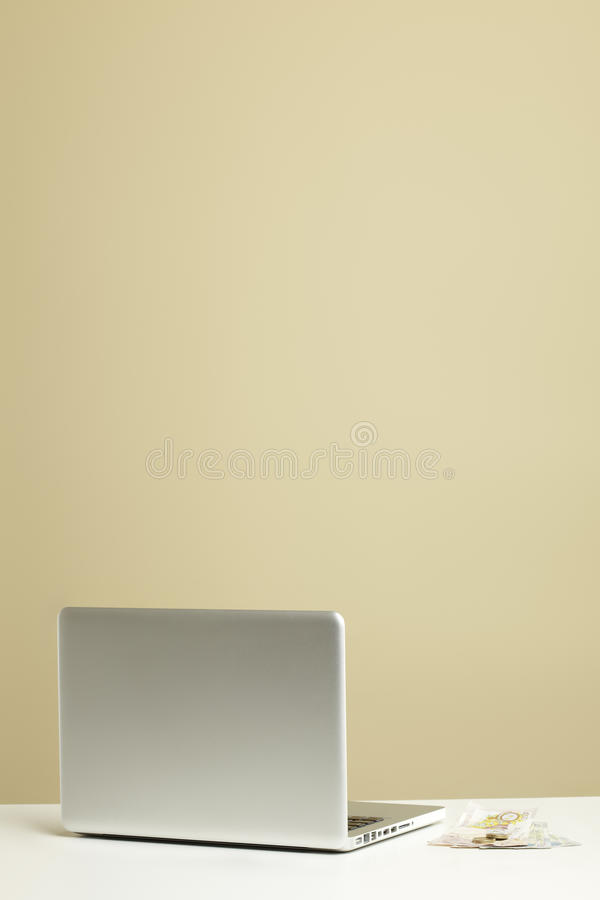 Laptop on desk with money stock photography