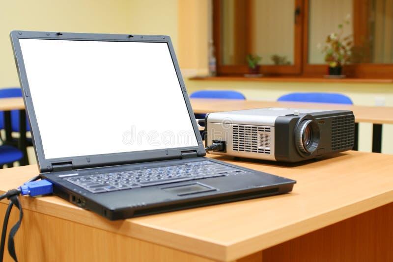 Laptop die aan projector op lijst wordt aangesloten stock foto
