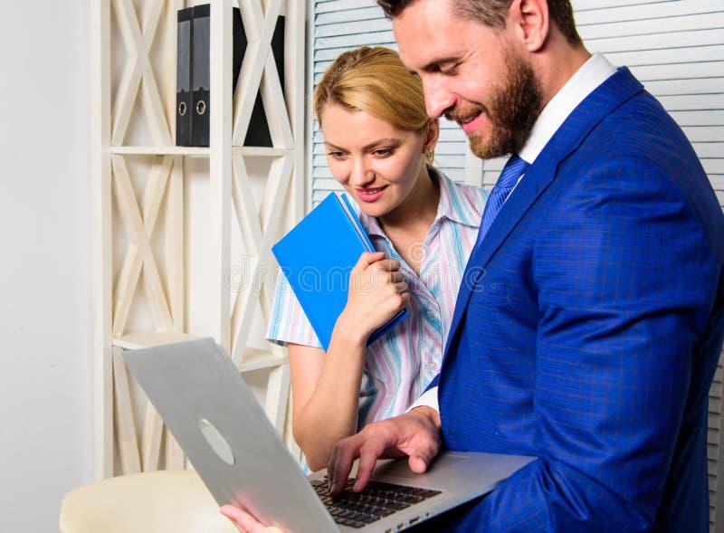 Laptop die van de zakenmangreep Internet met collega surfen De bureaupartner toont online de statistieken van informatiegegevens stock fotografie