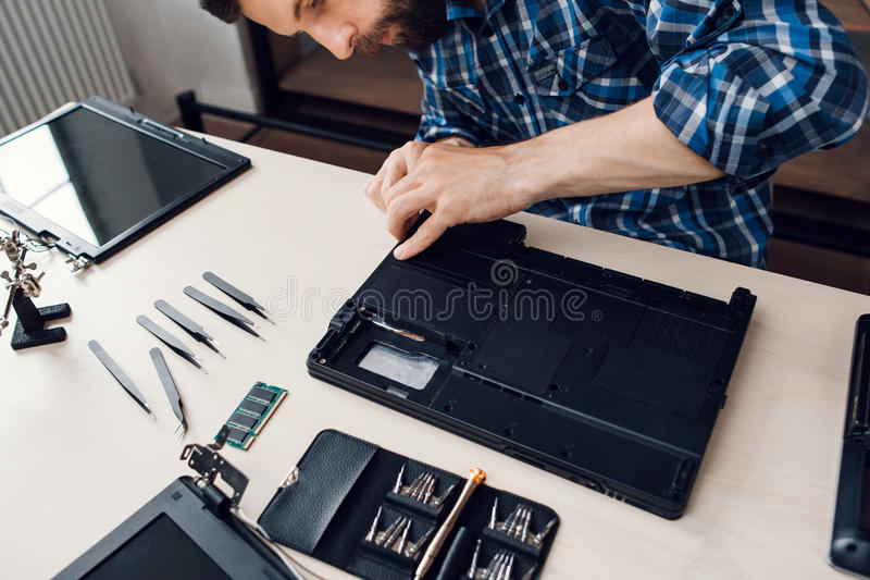 Laptop disassembling with screwdriver at repair. Engineer separate computer inside components from case. Electronic renovation, business, occupation concept royalty free stock photos
