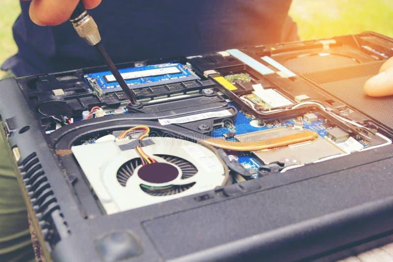 Laptop do reparo ou da elevação da chave de fenda da posse da mão do técnico na casa imagem de stock royalty free