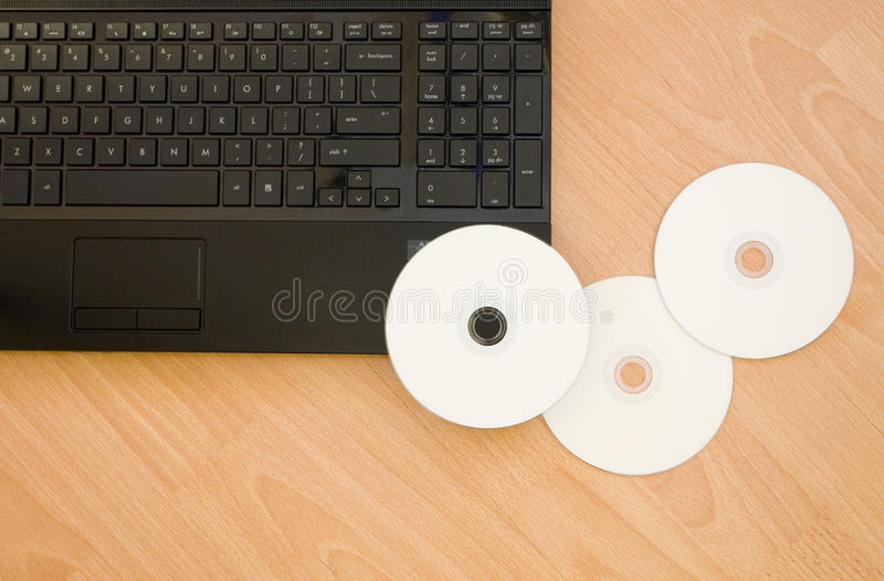 Laptop with DVD-rom. On Wooden Table stock images
