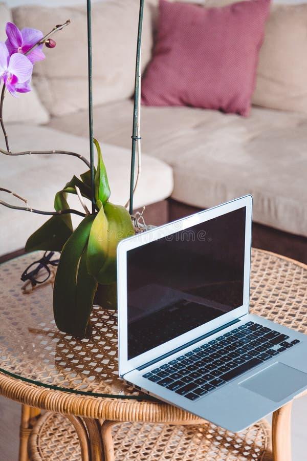 Laptop en een vaas met een orchidee bevinden zich thuis op een koffietafel, freelance werkplaats, blogger, marketing stock fotografie