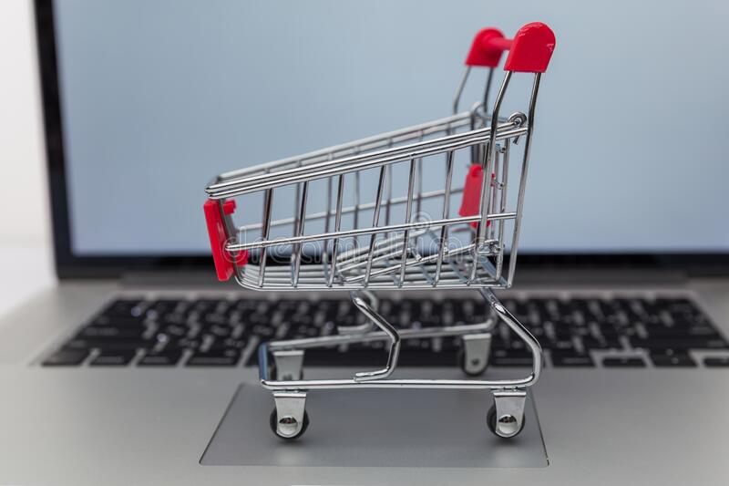 Laptop en klein karretje op witte achtergrond Internet shopping concept stock fotografie