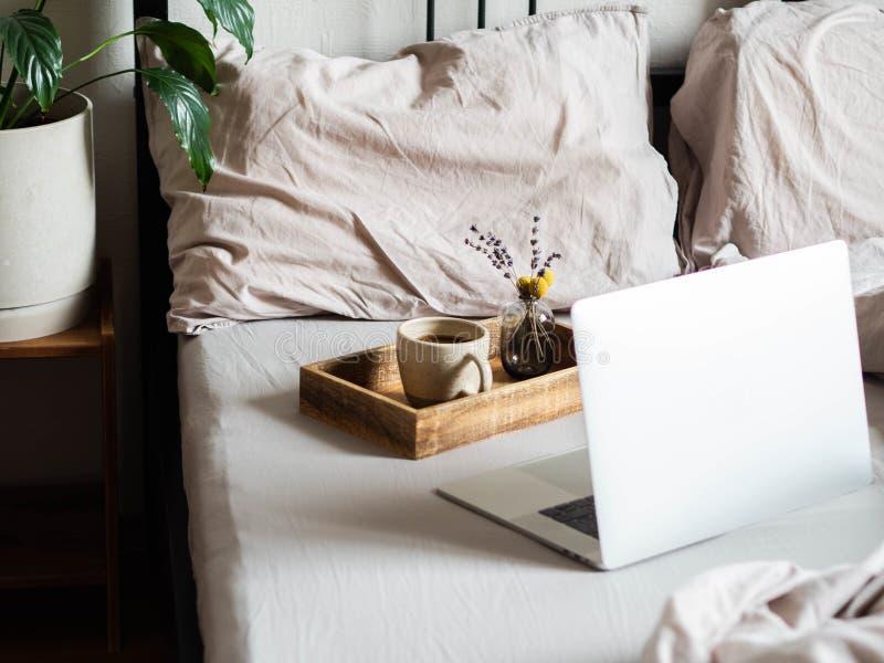 Laptop en koffie in de slaapkamer Thuis of comfortabele tijd online werken Blijf thuis, quarantaine Thuis werken royalty-vrije stock afbeelding
