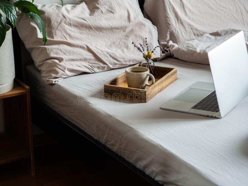 Laptop en koffie in de slaapkamer Thuis werken of een comfortabel tijdverdrijf online Blijf thuis, quarantaine Thuis werken royalty-vrije stock fotografie