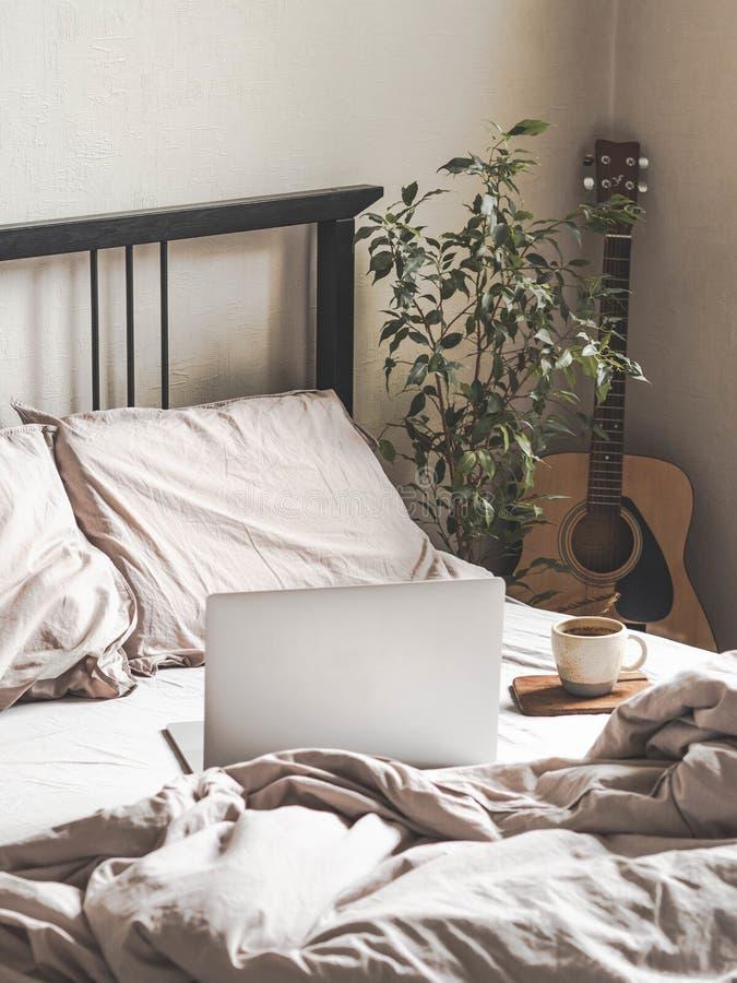 Laptop en koffie op bed en gitaar naast het bed in de slaapkamer Thuis of comfortabele tijd online werken Blijf thuis royalty-vrije stock afbeeldingen