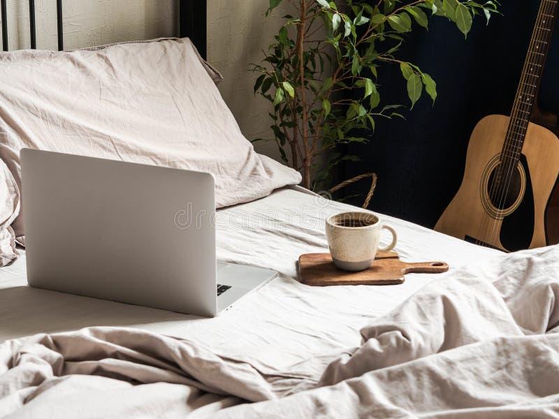 Laptop en koffie op bed en gitaar naast het bed in de slaapkamer Thuis werken of een comfortabel tijdverdrijf online Blijf hier royalty-vrije stock foto's