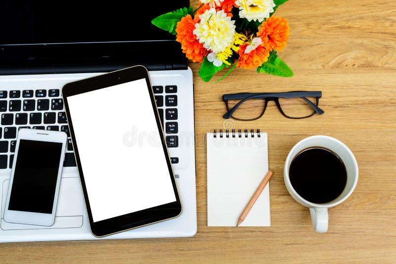 Laptop en kop van koffie met bloem op bureau stock foto