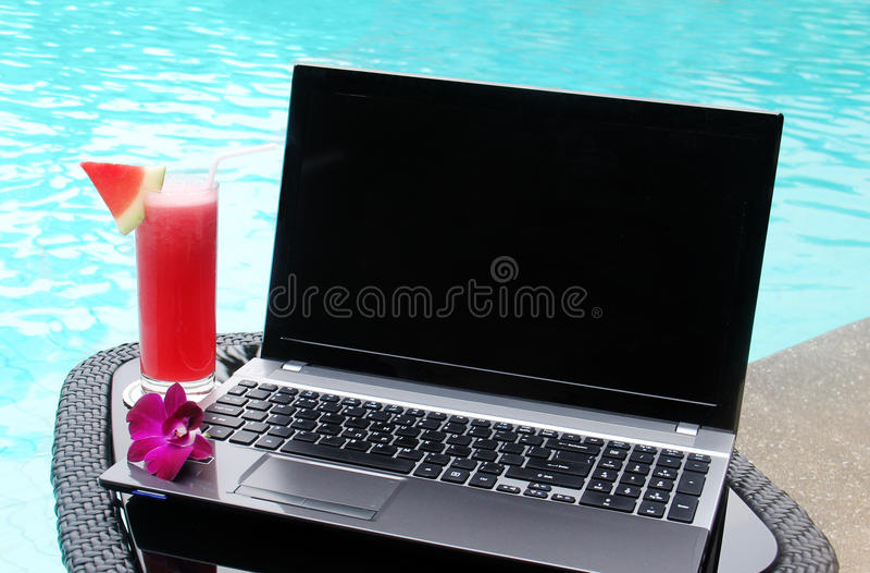 laptop en watermeloensappoolside stock afbeeldingen