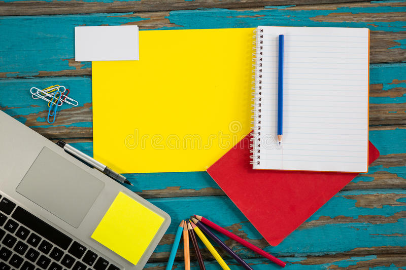 Laptop with files and spiral notebook. On table stock photos