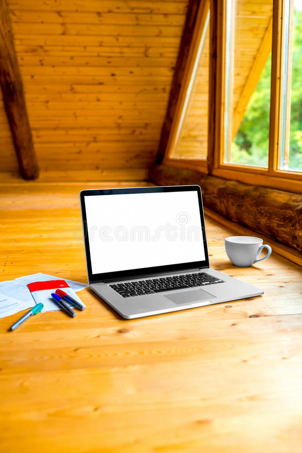 Laptop on the floor with markers and coffee cup. Laptop with empty screen, markers and coffe cup on the wooden floor near the window in the cottage royalty free stock image
