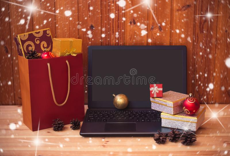 Laptop, gifs and shopping bag full of christmas gifts royalty free stock photo