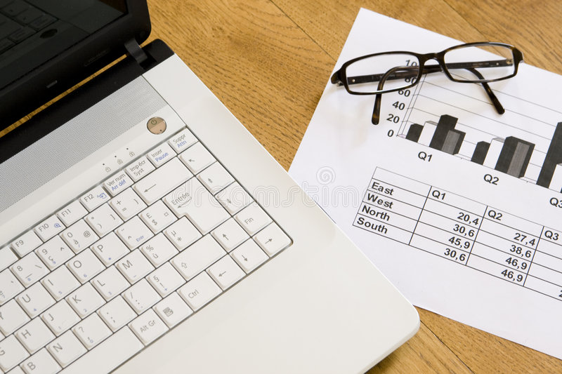 Laptop, glasses and charts stock photo