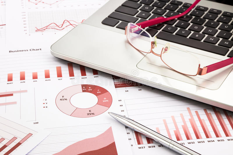 Laptop and glasses with red business charts, graphs, research an. D reports background for management and business concepts stock photo