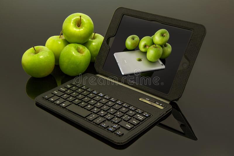 Laptop and green apples royalty free stock image