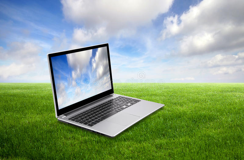 Laptop on green grass royalty free stock photography