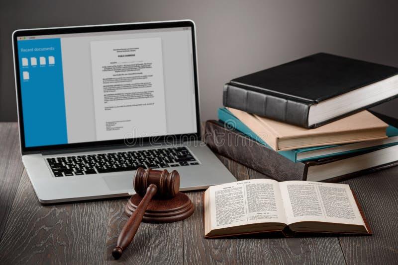 Laptop, Hammer und Bücher lizenzfreie stockbilder