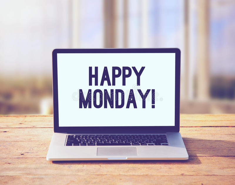 Laptop with happy Monday wish. On wooden boards table on office sunlight morning background royalty free stock photo
