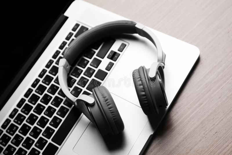 Laptop and headphones on a table. Close up stock photography