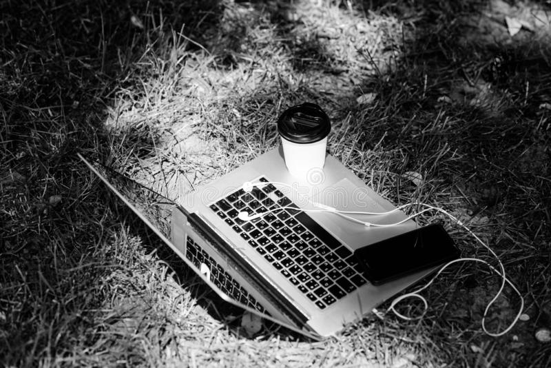 Laptop with headset of mobile phone and coffee to go on green grass. agile business. Online study. summer vibes. Relax. University students life. Online stock photos