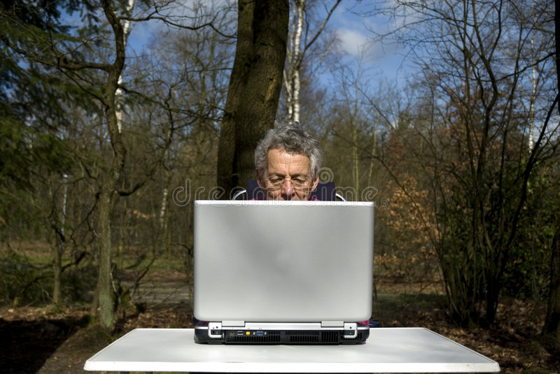 Laptop at home. Senior man with laptop in the nature stock photos