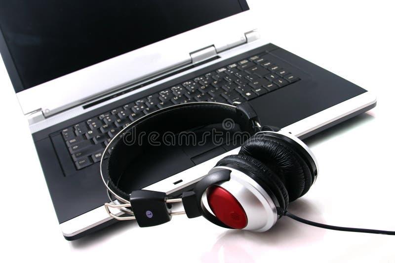 Laptop, hoofdtelefoons stock afbeelding