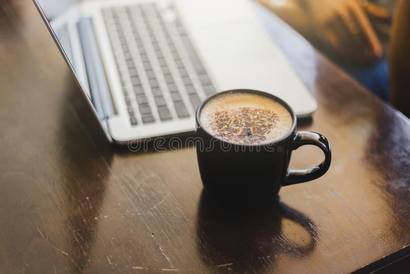 Laptop i filiżanka przy jego pracującym miejscem w kawiarni fotografia royalty free