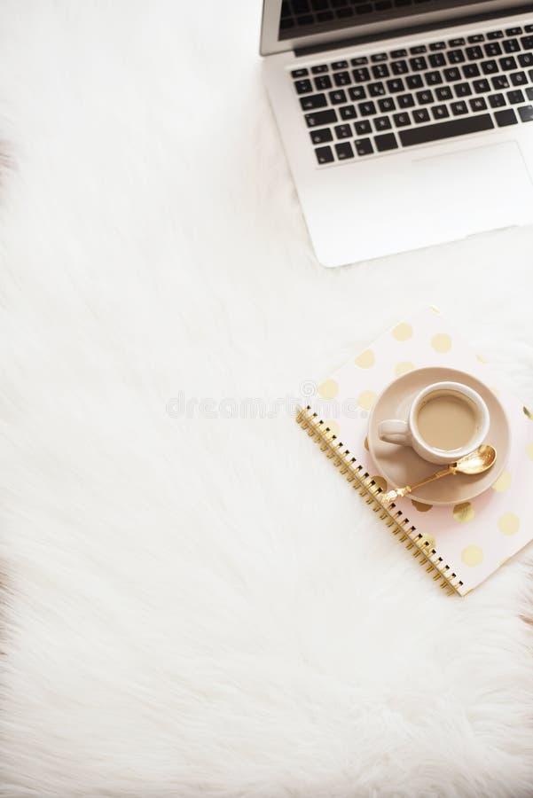 Laptop, kawa i notatnik na podłoga na białym futerkowym dywanie, Freelance mody kobiecości domu wygodny workspace w płaskim losie obraz stock