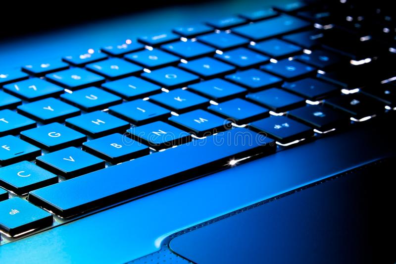 Laptop keyboard as a background toned to blue stock photo