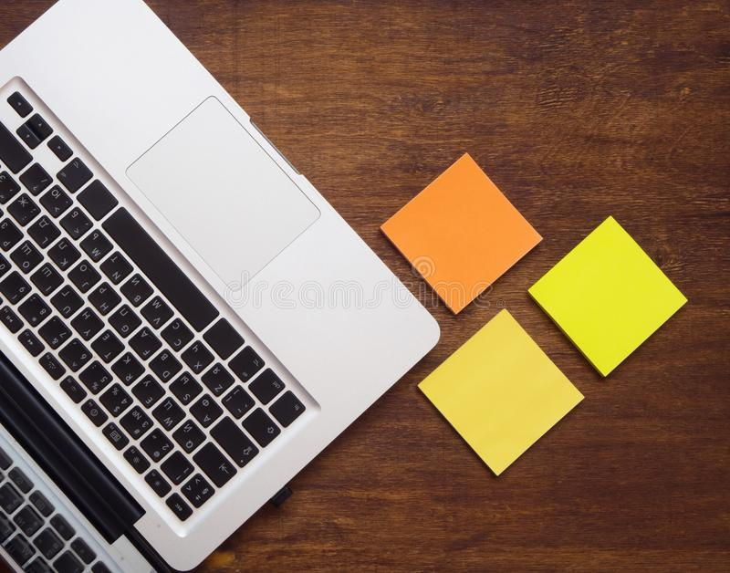 Laptop keyboard and yellow and orange stickers view from above royalty free stock photo