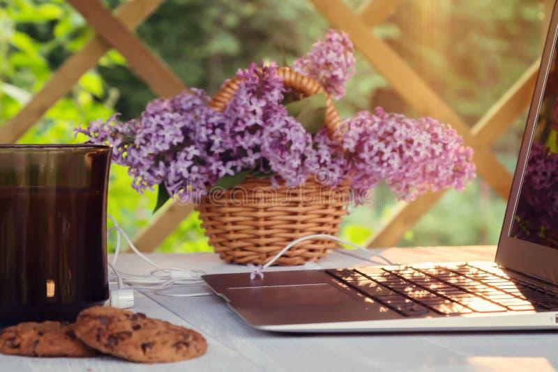 Laptop, kop van koffie, koekjes en een mand van lilac bloemen op een witte houten lijst in het de zomerterras - concept van royalty-vrije stock foto's