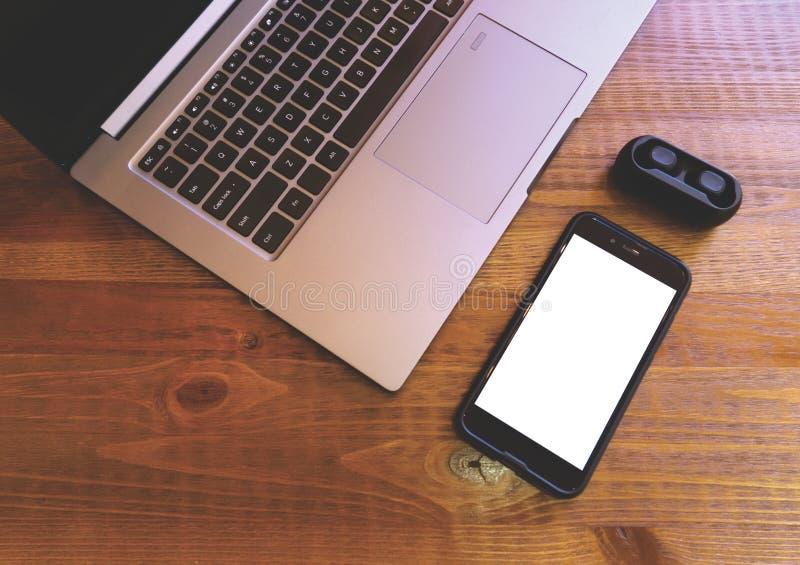 Laptop lege mobiel en hoofdtelefoons op houten achtergrond Spot omhoog met het lege smartphonescherm en tws hoofdtelefoon modern stock afbeelding