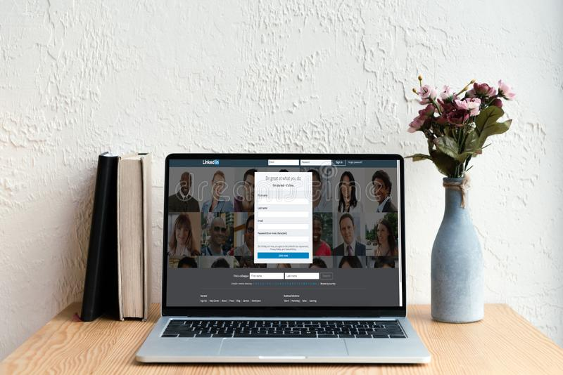laptop with linkedin website on screen books and flowers in vase royalty free stock image