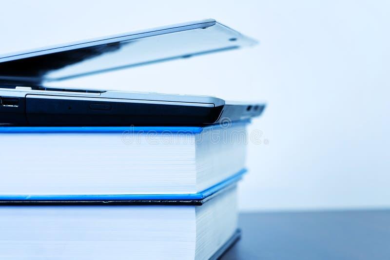 Laptop lying on books stock photo