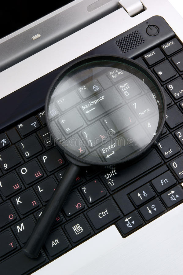 Laptop with a magnify glass royalty free stock image