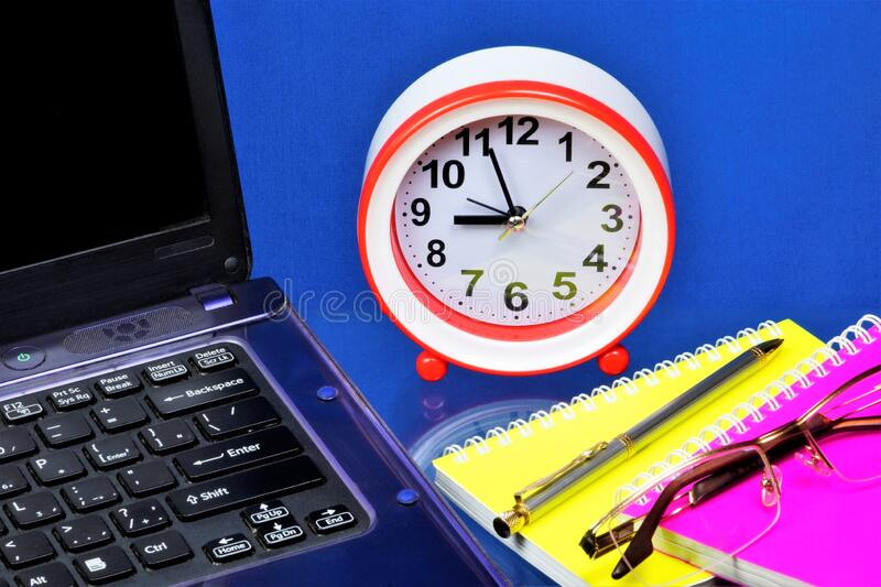 A laptop for the Manager`s work, a clock is a symbol of time, a reminder of the past and the future. Notepad, glasses, and pen fo royalty free stock photo
