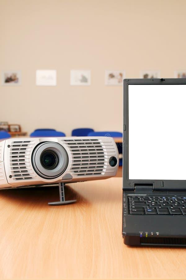 Laptop met de projector op bureaulijst stock afbeelding