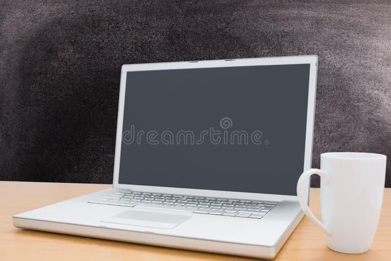 laptop met koffiemok op bordachtergrond royalty-vrije illustratie