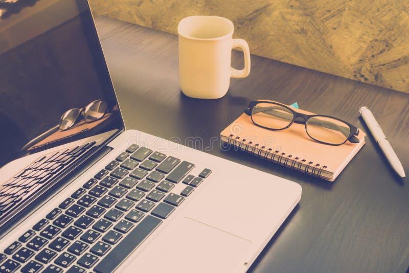 Laptop met kop van koffie, notitieboekje, glazen en pen op het bureau, royalty-vrije stock fotografie