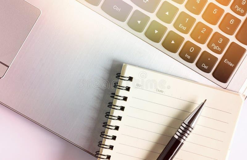 Laptop met notitieboekjepen met zonlichteffect royalty-vrije stock afbeeldingen