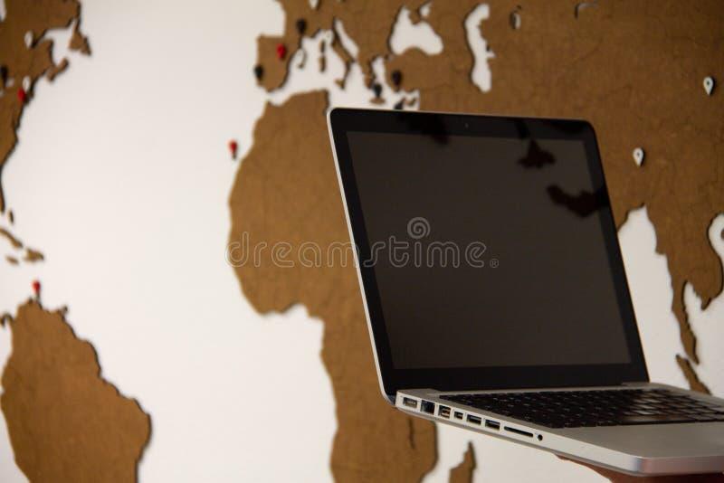 Laptop met op de achtergrond worldmap royalty-vrije stock afbeeldingen